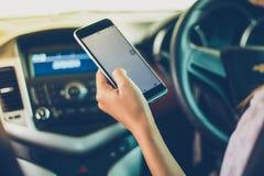 Asiatinnen fahren Autos und benutzen einen Smartphone auf der Straße stockfotografie