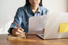 Asiatinnen nehmen Kenntnisse mit einem Bleistift im Büro, Geschäftsfraufunktion stockfotografie