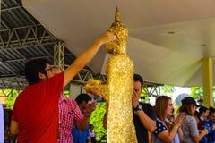 Asiatinnen und Männer haften eine Platte des Goldes auf dem Buddha lizenzfreie stockfotos