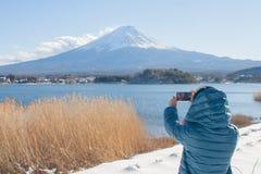 Asiatinreisender, der Fotografie die schöne Landschaftsansicht von Fuji-Berg umfasst mit weißem Schnee im Winter saisonal vertrit lizenzfreie stockfotografie