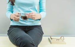 Asiatinrest für Getränkkaffee in der transparenten Glasschale in ihrer Hand in ihrer Freizeit im Raum mit hölzernem Schreibtisch  Lizenzfreies Stockbild