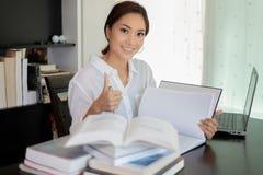 Asiatinstudentenlächeln und -Bums herauf Handzeichen und a -lesend lizenzfreie stockfotos
