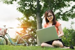 Asiatique de femme employant le concept extérieur d'ordinateur portable Photographie stock