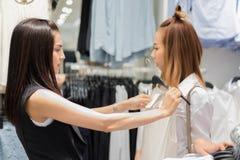 Asiatique de sourire de la jeune femme deux avec des achats et achat au mail/au supe Photos stock