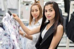 Asiatique de sourire de la jeune femme deux avec des achats et achat au mail/au supe Photographie stock libre de droits