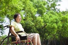 Asiatische ältere Frau, die auf einem Rollstuhl sitzt Lizenzfreie Stockfotografie