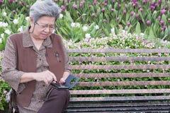 Asiatische ältere Frau, die intelligentes Mobiltelefon hält, während das Sitzen auf ist Lizenzfreie Stockfotos