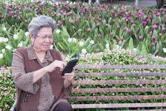 Asiatische ältere Frau, die intelligentes Mobiltelefon hält, während das Sitzen auf ist Stockfoto