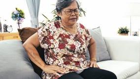 Asiatische ältere Frau, die zu Hause unter den Schmerz in der Rückseite oder in den Zügeln leidet stock video