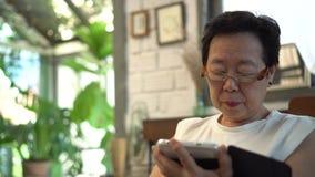 Asiatische ältere Frau mit Glassehvermögenproblem, Belastung vom digitalen Lebensstil