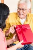 Asiatische ältere Paare in der lächelnden Liebe beim Halten des Geschenks Stockfoto