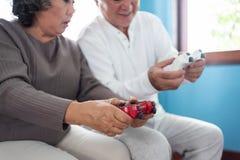 Asiatische ältere Paare, die Steuerknüppel halten und Videospiele zu spielen lizenzfreies stockbild