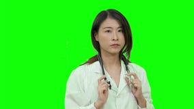 Asiatische Ärztin, die auf grünem Schirm denkt stock footage