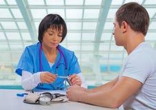 Asiatische Ärztin, die auf medizinischem Thermometer und sitzendem a schaut Lizenzfreies Stockbild