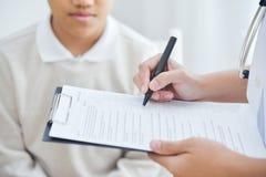 Asiatische Ärztin, die Kenntnis über Checkliste für ein PA des kleinen Jungen nimmt Stockbild