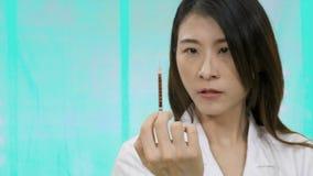 Asiatische Ärztin, die Spritze zusammendrückt stock footage