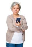 Asiatische alte Frau gelesen auf dem Smartphone stockbilder
