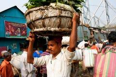 Asiatische Arbeitskraft mit einem schweren Wagen auf dem Kopf Lizenzfreies Stockbild