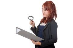 Asiatische Büromädchen-Gebrauchslupenkontrolle auf Daten Lizenzfreie Stockbilder