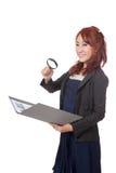 Asiatische Büromädchen-Gebrauchslupenkontrolle auf Daten und Lächeln Stockbild
