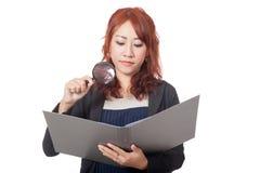 Asiatische Büromädchen-Gebrauchslupenkontrolle auf einem Ordner mit Ba Lizenzfreies Stockbild
