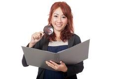 Asiatische Büromädchen-Gebrauchslupenkontrolle auf einem Ordner und einem SMI Lizenzfreie Stockbilder