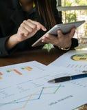 Asiatische berufstätige Frau und Tablette an Hand mit Geschäftszusammenfassungs- oder Unternehmensplanbericht mit Diagrammen und  Lizenzfreies Stockfoto