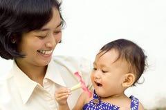 Asiatische berufstätige Mutter und Schätzchen Stockbilder