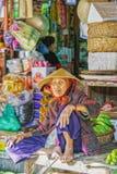 Asiatische blinde alte Frau, die Bündel Bananen im Markt verkauft Stockfotos