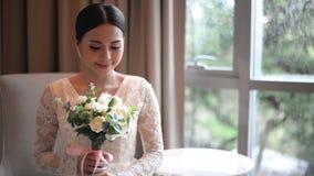 Asiatische Braut in der Spitzekleiderholding und in der schönen weißen Hochzeit des Geruchs blüht stock video footage