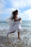 Asiatische Braut, die entlang den Strand läuft Stockfotografie