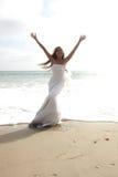 Asiatische Braut, die ihre Freude auf dem Strand feiert Stockfoto