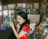 Asiatische Braut in rotem cheongsam Kleid, das auf ihren Lippenstift sich setzt Stockbild