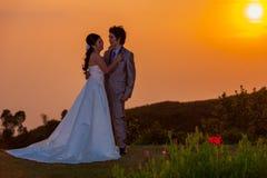 Asiatische Braut und Bräutigam Standing auf Berg bei Sonnenuntergang Stockbild