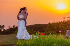 Asiatische Braut und Bräutigam Standing auf Berg bei Sonnenuntergang Lizenzfreies Stockbild