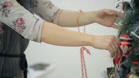 Asiatische Brunettefrau verziert auf Weihnachtsbaum während des neuen Jahres stock video footage