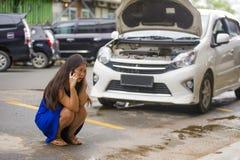 Asiatische Chinesin im Druck angeschwemmt auf dem leidenden Automotortriebwerkausfall der Straße, der Mechanikerproblem nennend z lizenzfreie stockfotografie