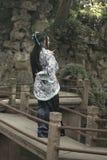 Asiatische Chinesin in traditionellem blauem und weißem Hanfu-Kleid, Spiel in einem berühmten Garten auf gekrümmter Brücke lizenzfreie stockfotografie