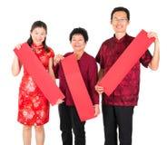 Asiatische chinesische Familie, die roter Frühling Couplets anhält lizenzfreies stockfoto