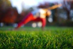 Asiatische chinesische Frau, die Yoga in der Natur während des Sonnenuntergangs tut Stockfotografie