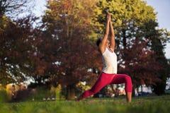 Asiatische chinesische Frau, die Yoga in der Natur während des Sonnenuntergangs tut Stockbilder