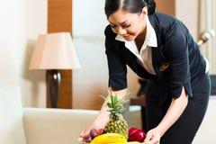 Asiatische chinesische Hotelhaushälterin, die Frucht setzt Stockfotos