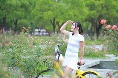 Asiatische chinesische junge schöne, elegant gekleidete Frau mit dem Teilen des Fahrrades Schönheit, Mode und Lebensstil Lizenzfreie Stockfotos