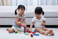 Asiatische chinesische kleine Schwestern, die Blöcke auf dem Boden spielen Lizenzfreie Stockbilder