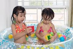Asiatische chinesische kleine Schwestern, die im aufblasbaren Pool spielen Lizenzfreie Stockfotos