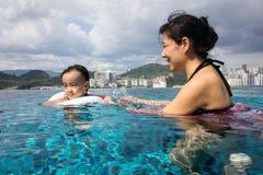 Asiatische chinesische Mutter und daugther, die am Swimmingpool spielt Stockbilder