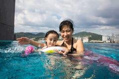 Asiatische chinesische Mutter und daugther, die am Swimmingpool spielt Stockbild