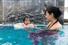 Asiatische chinesische Mutter und daugther, die am Swimmingpool spielt Stockfotografie