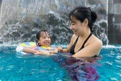 Asiatische chinesische Mutter und daugther, die am Swimmingpool spielt Lizenzfreies Stockfoto