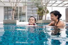 Asiatische chinesische Mutter und daugther, die am Swimmingpool spielt Lizenzfreie Stockfotos